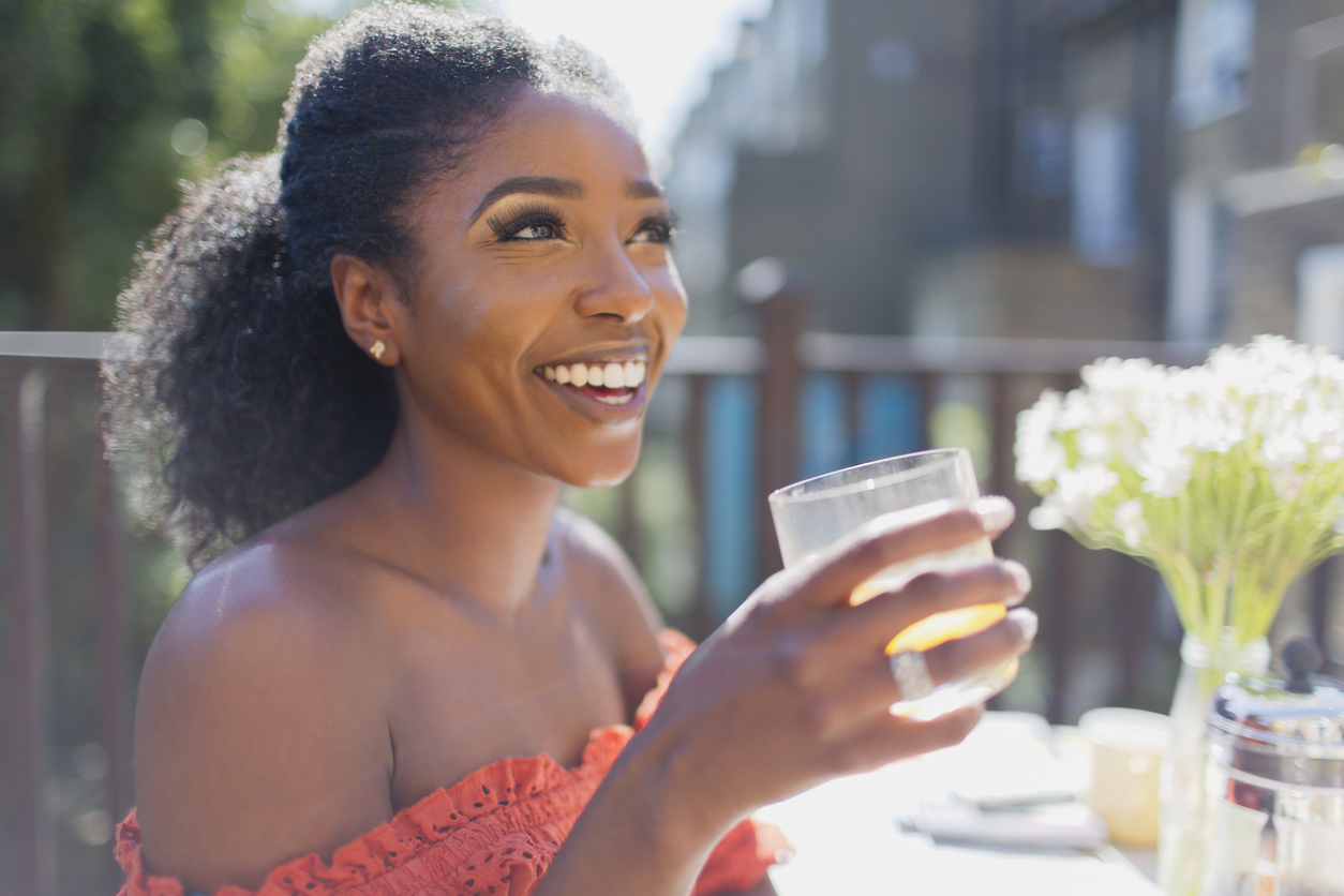 Happy young woman drinking orange juice on sunny balcony