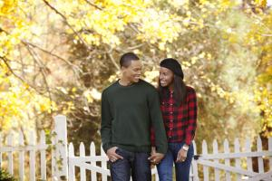 Young Couple Holding Hands and Walking Through Fall Leaves