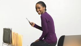 Young woman with cell phone sitting on desk