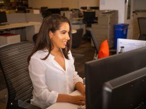 Latino Woman At Desk Smiling