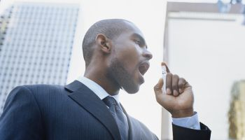 Businessman using breath freshener outdoors, low angle view