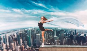 Ballet dancer stand on the edge on roof top above New York City
