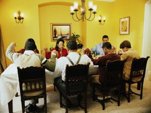 Family saying grace at dinner table