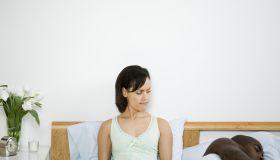Mixed Race woman looking at sleeping boyfriend